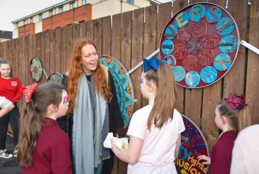 One of the artists with young people who were involved with the mosaic