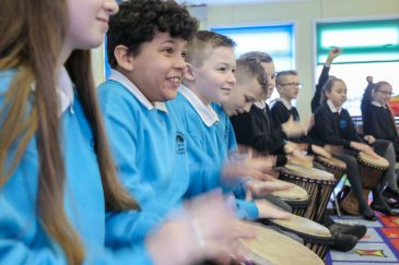 Pupils enjoying taking part in a drumming workshop