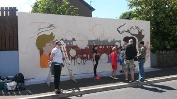 Young people starting to add the colour to the outline.