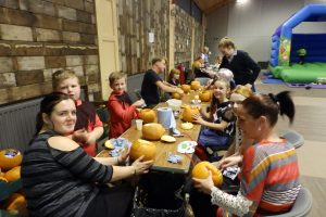 Everyone enjoying the pumpkin carving.