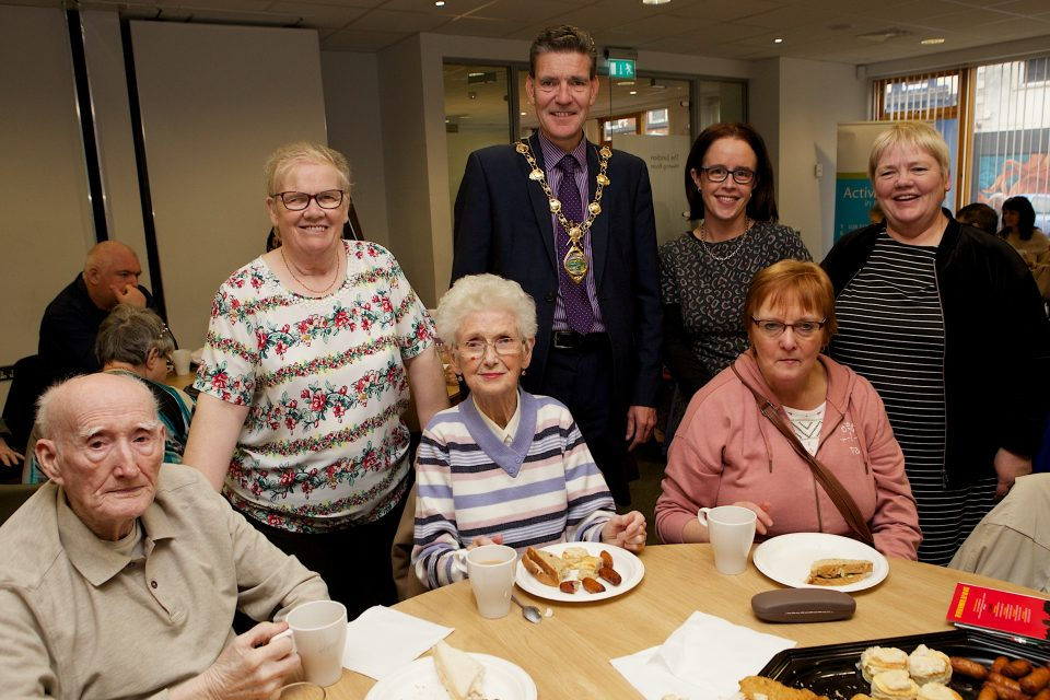 Mayor John Boyle at the Apex Older Persons Day held in Holywell Trust, with, on left, Bridie McCallion, and from right, Barbara Carlin and Anne McCorkell, Apex. Seated, from left, are Jim and Rita Harris and Kathleen McMenamin.