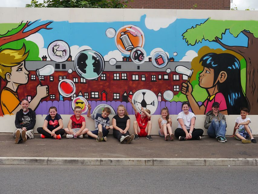 Young people from Ballynafoy Close with the finished art work and artists.