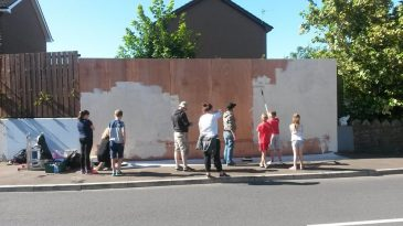 Young people starting to prepare the wall to be painted.